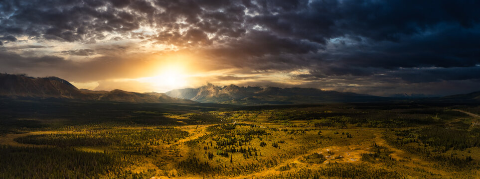 Beautiful Panoramic View of Lush Forests, Trees and Land surrounded by Mountains in Canadian Nature. Dramatic Colorful Sunset Sky. Aerial Drone Shot. Taken near Alaska Highway, Yukon, Canada.