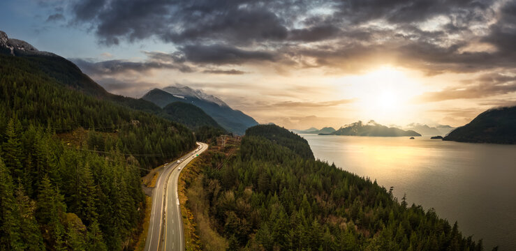 Sea to Sky Hwy in Howe Sound near Squamish, British Columbia, Canada. Aerial panoramic View. Dramatic Colorful Sunset Sky Art Render.