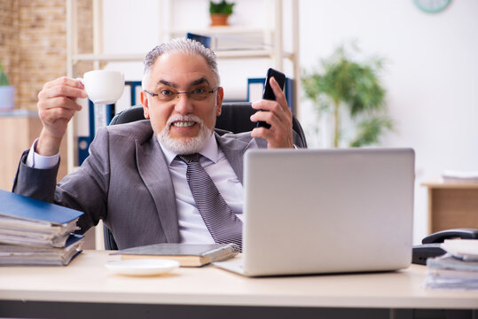 Old male employee drinking coffee in the office