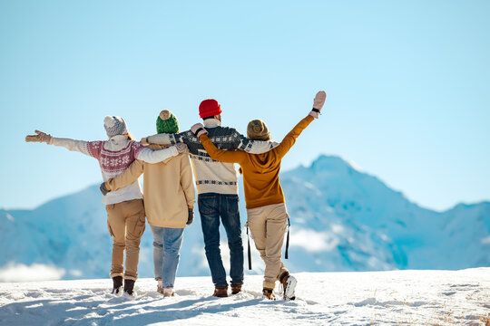 Happy friends embracing against snow capped mountains