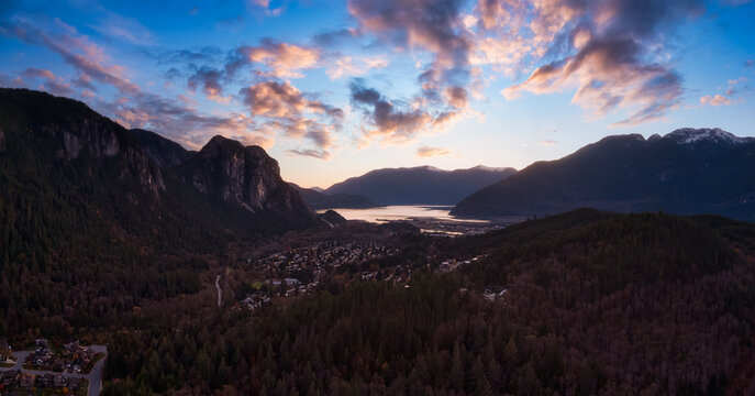 Squamish, North of Vancouver, British Columbia, Canada. Beautiful Aerial Panoramic View of a small town surrounded by Canadian Nature during Autumn Season. Dramatic Sunset Sky.
