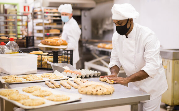 Working at bakery during coronavirus outbreak, man in mask for viral protection kneading dough and shaping baguettes on steel countertop in industrial kitchen