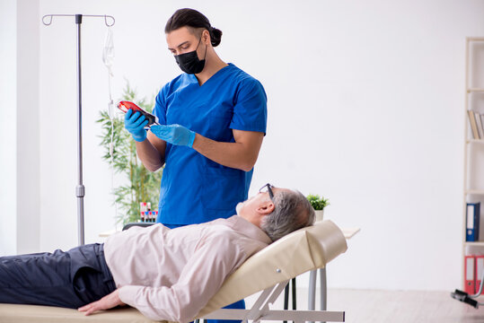 Old patient visiting young male doctor for intravenous therapy