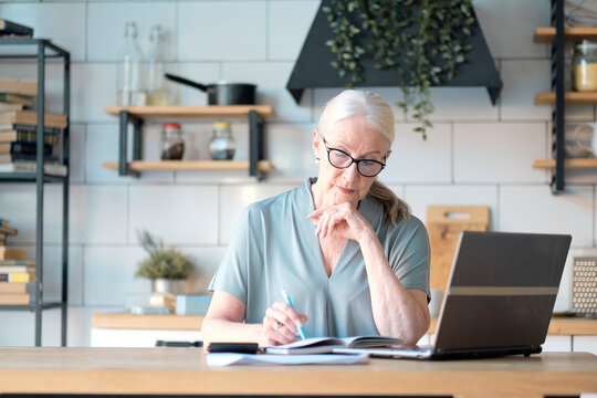 Senior woman using laptop for websurfing in her kitchen. The concept of senior employment, social security. Mature lady sitting at work typing a notebook computer in an home office.
