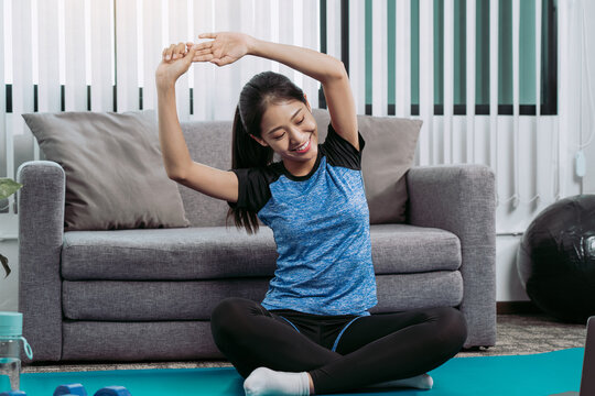 Young Asian woman stretching after her workout at home.