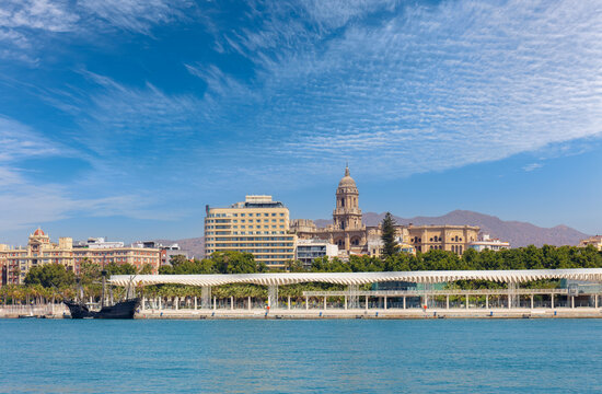 View of the port and skyline of the Spanish port city of Malaga in Andalusia. It's a summer day with blue skies. On the left is a historic sailing ship. In the background are mountains.