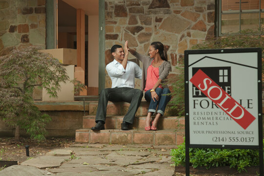 Couple sitting on front stoop of house with sold sign