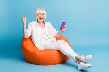 Photo portrait of granny using cellphone laughing gesturing like winner isolated on vibrant blue...