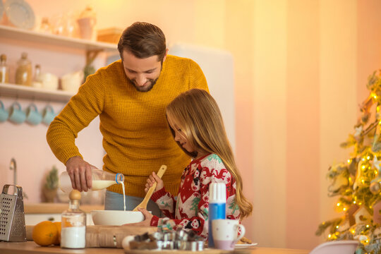 Girl and her dad stirring something in a bowl and smiling