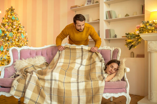 Caring husband covering his napping wife with a plaid