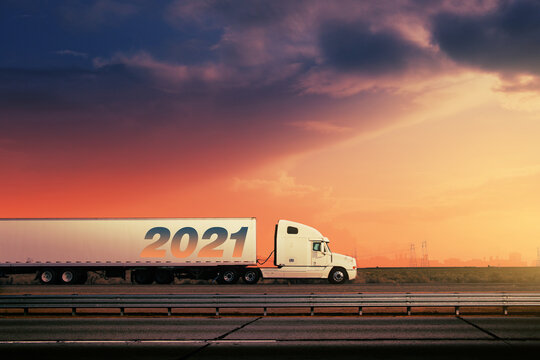 White 2021 freight truck driving on freeway road, fiery sunset sky city skyline in background.