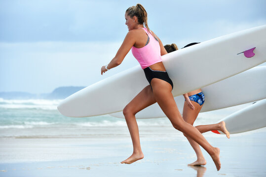 Side view of team of female surf lifeguards training and running into sea holding ocean surf skis