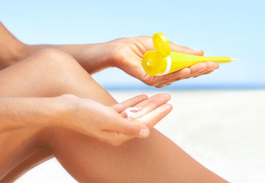 Close up of young woman squirting sunscreen from yellow tube into her hand ready to apply to her legs