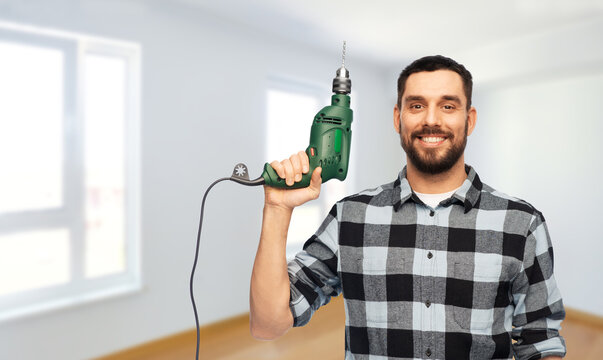 repair, construction and work concept - happy smiling man, worker or builder with drill over room with building equipment background