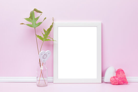 Feminine picture frame mockup. Template with white vertical frame, heart-shaped ornaments and fern leaves in front of pink wall. Blank image area masked with clipping path