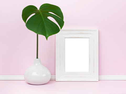 Elegant feminine picture frame mockup with monstera leaf in vase in front of pink wall.Blank image area masked with clipping path