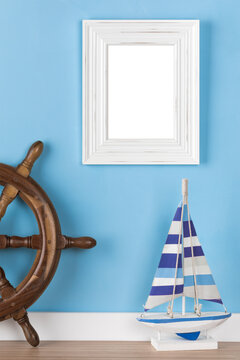 Maritime picture frame mockup with sail boat  and helm in front of blue wall. Blank image area masked with clipping path