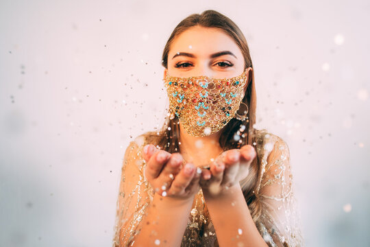 Covid-19 Xmas. Holidays congratulation. Quarantine winter holidays celebration. Happy woman in gold chain face mask blowing bokeh light sparkles from hands open palms on pink empty space background.