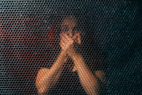 Keep quiet. Family abuse. Female rights. Stop talking. Textured portrait of scared terrified woman covering mouth with hands behind plastic bubble wrap wall alone in darkness.