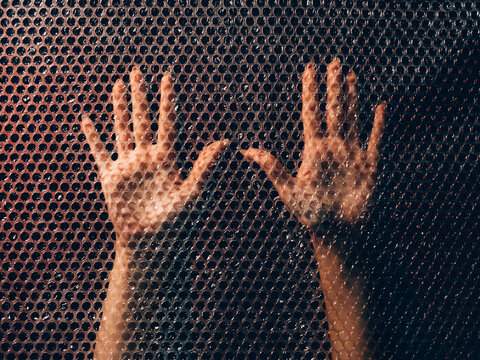 Sensual female hands. Loneliness melancholy. Passion desire. Tender woman open palms touching transparent plastic bubble wrap texture wall in darkness.