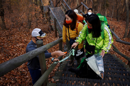 Members of Clean Hikers collect litter while hiking a mountain in Incheon, South Korea
