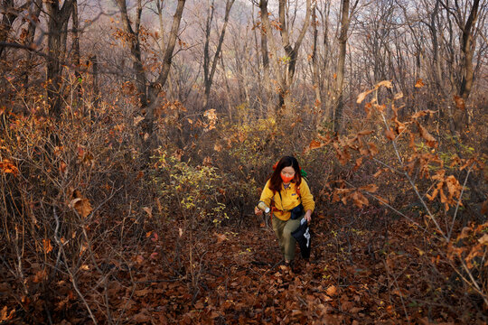 Kim Kang-Eun, an artist who leads Clean Hikers, collects litter while hiking a mountain in Incheon, South Korea