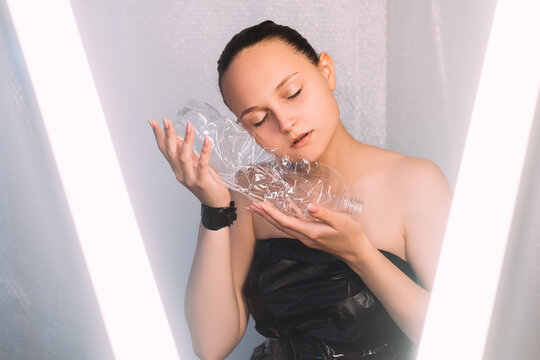 Zero waste. Plastic recycling. Environmental protection. Caring woman in black garbage bag dress pampering used disposable bottle in white illumination on light bubble wrap background.