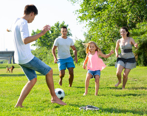 Positive parents with two kids playing soccer together on green field on summer day. High quality...