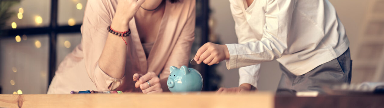 Mother and child putting coin into piggy bank. Education of children in financial literacy. Money, cash, investment.