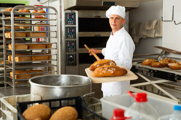 male baker with bread on baking shovel in kitchen