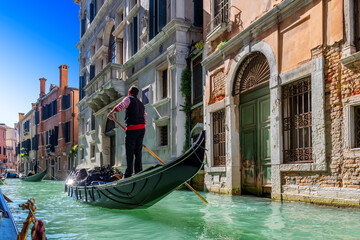 A Venetian gondolier rules a gondola through the waters of the Venice canal, Venice, Italy