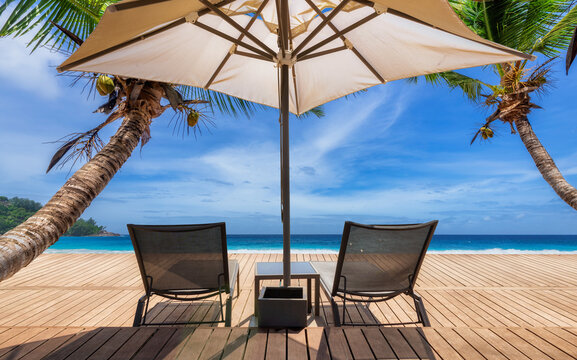Paradise Sunny beach with umbrella and deckchairs on wooden floor, palm trees and the turquoise sea on Tropical island.