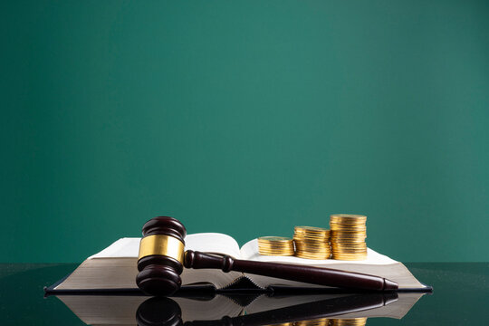 Stack Of Coins With Gavel Over Open Book On Table Against Green Background