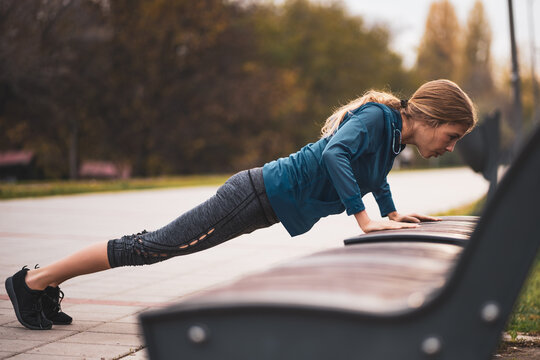 Beautiful adult woman is exercising outdoor on cloudy day in autumn. She is doing push-ups.