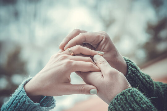 A man puts a ring on a girl's finger. a couple in love