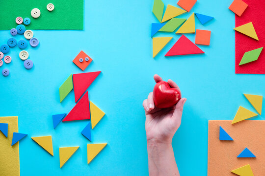 Geometric design for Autism World day with tangram puzzle triangles, pictogram and hand with heart