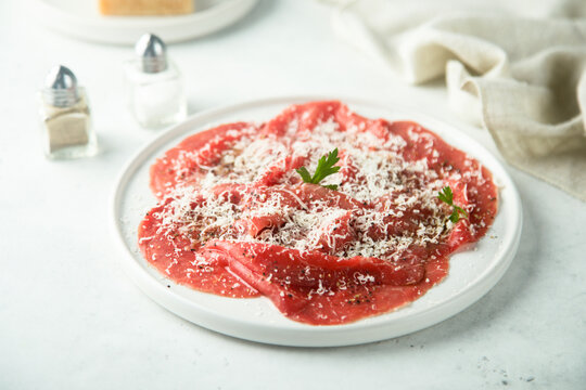 Traditional Italian beef carpaccio with grated cheese