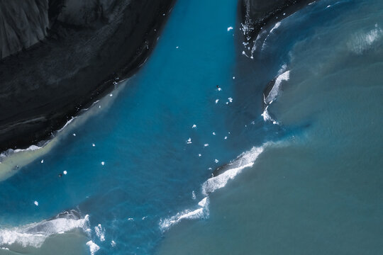 Aerial photo of the Black sand beach coastline in Iceland with small ice chunks