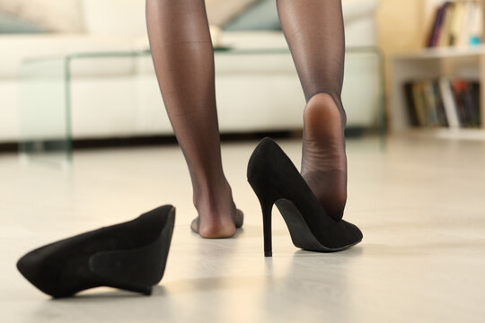 Woman arriving home after work undressing taking off shoes