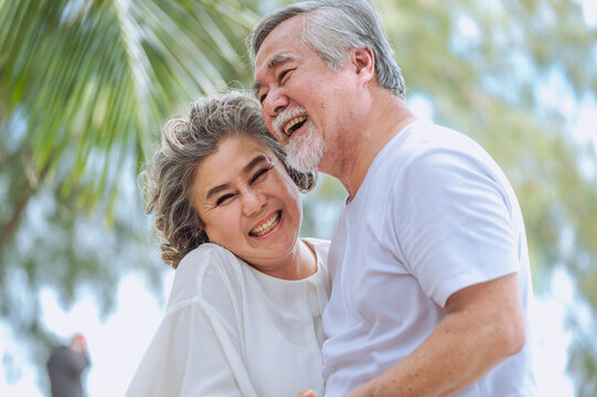 Happy asian senior retired couple, relax smiling elder man and woman enjoying with retired vacation at sea beach outdoor. Health care, Family outdoor lifestyle