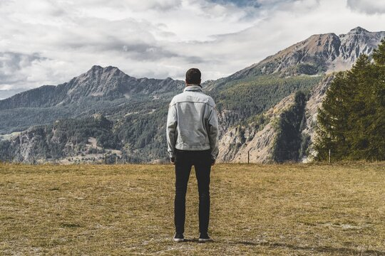 Rear View Of Man Looking At Mountains While Standing On Field