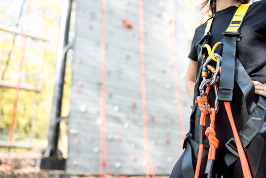 Close-up of safety equipment for climbers weared on the woman with climbing wall on the background