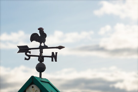 Weather Vane On Rooftop Against Cloudy Sky