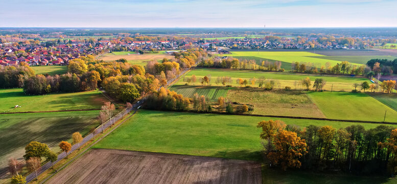 Aerial view of the flat landscape in the north of Germany with a village in the background against the straight horizon
