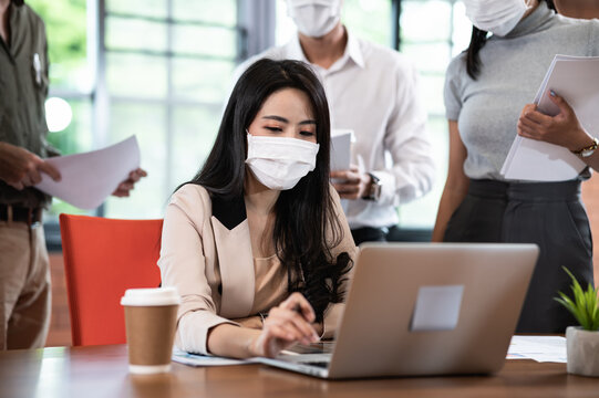 Attractive Asian female boss supervisor wear protective face mask in New normal office teaching and explaining intern or new employee to use corporate software or helping with difficult assignment