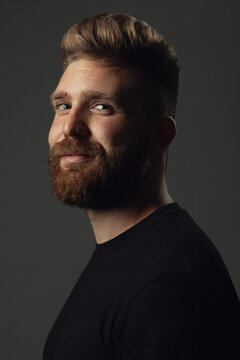 Fabulous at any age. Portrait of smiling 35-year-old man posing over gray background in black t-shirt. Close up. Hipster style. Red hair, modern haircut. Studio shot