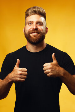 Thumbs up concept. Portrait of happy, smiling 35-year-old man with fit body posing over yellow background in black t-shirt. Hipster style. Red hair, modern haircut. Studio shot
