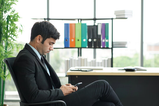Side View Of Businessman Using Mobile Phone While Sitting In Office