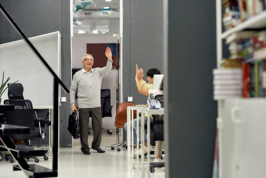 Full length shot of cheerful aged man, senior intern saying goodbye to his young colleagues while leaving office after first day at work