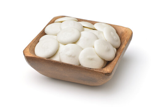 Wooden bowl of white chocolate buttons
